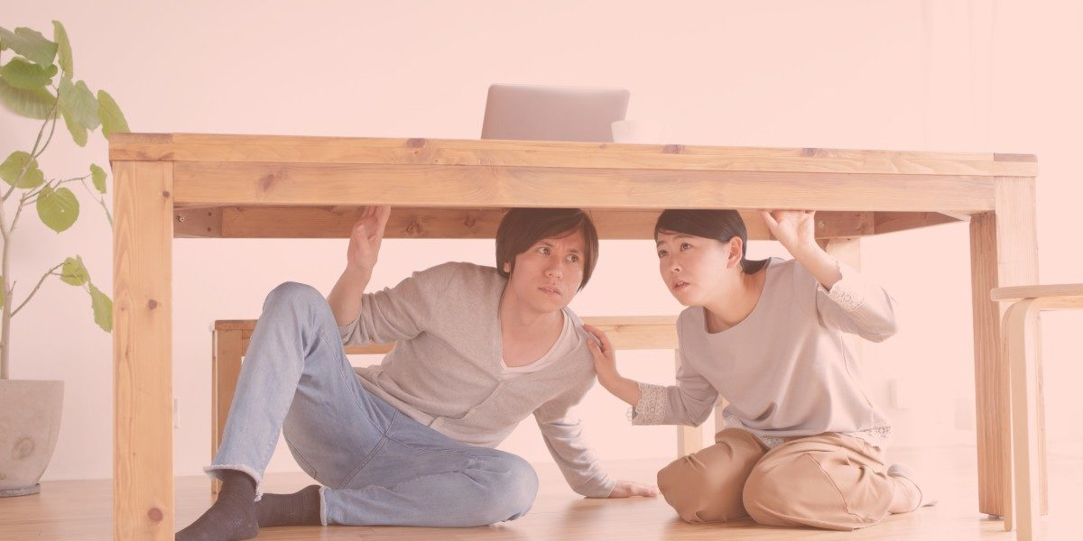 Two adults sheltering under table during earthquake