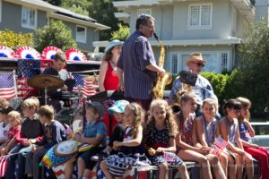 a band surrounded by children at a Berkeley July 4th neighborhood parade