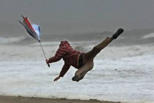 person on a beach being blown in the air from wind